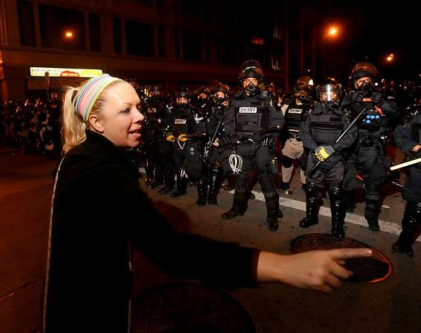 Occupy Oakland protester Anna Buschman calls for peace as sheriff's deputies approach on demonstrators on Thursday, Nov. 3, 2011, in Oakland, Calif. Following a mainly peaceful day-long protest by thousands of anti-Wall Street demonstrators, several hundred rallied through the night with some painting graffiti, breaking windows and setting file to garbage cans. (AP Photo/Noah Berger) Photo: Noah Berger, AP