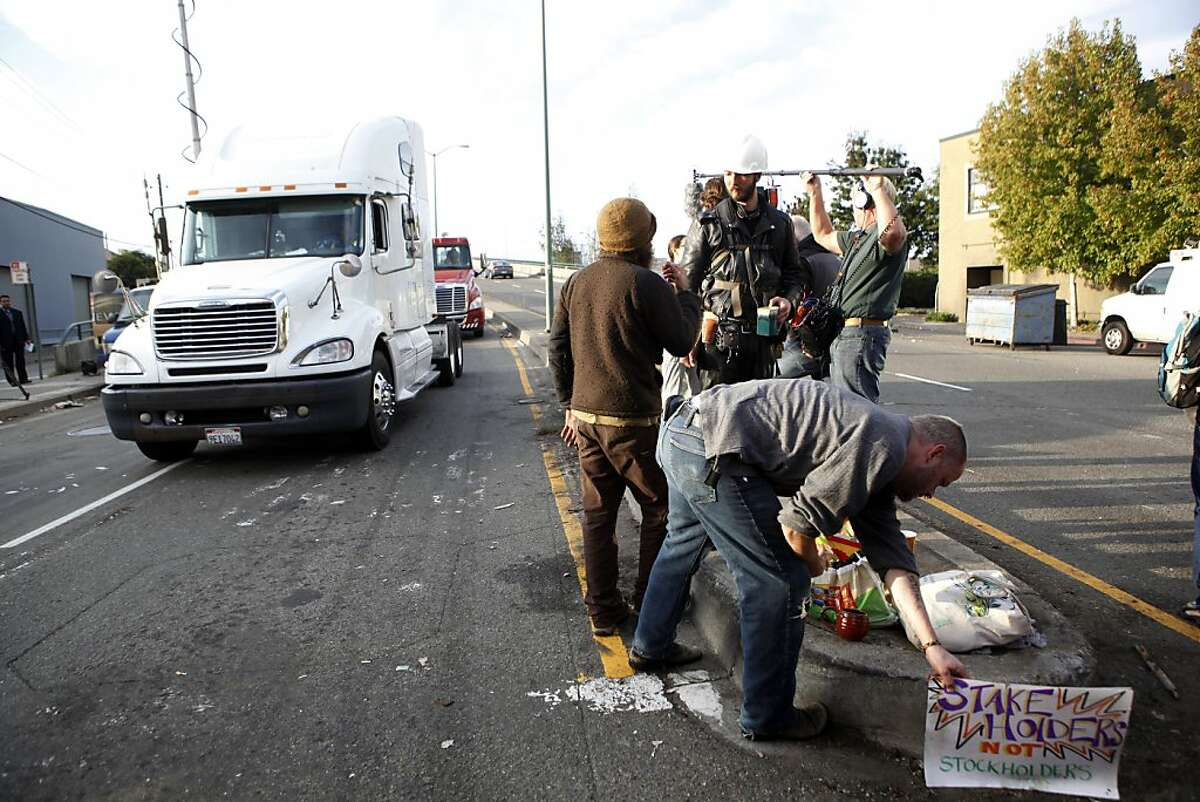 Protestors clean up after giving up a barricade to the port's entrance at 3rd Street and Adeline early Thursday, November 3, 2011 in Oakland, Calif.