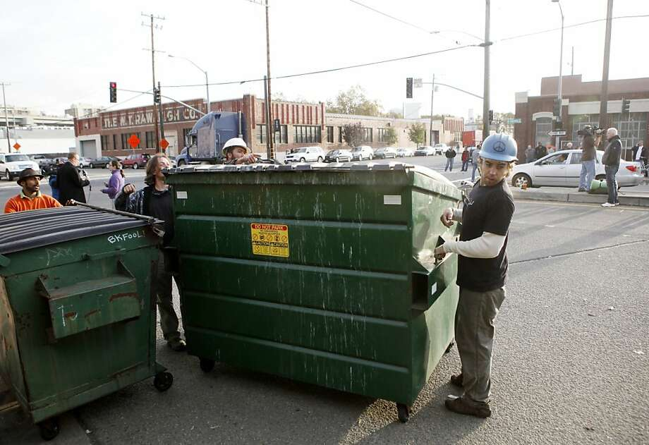 Aaron Thomas, (right) of Oakland, helps remove a dumpster which had been used to barricade the port's entrance at 3rd Street and Adeline early Thursday, November 3, 2011 in Oakland, Calif. Photo: Beck Diefenbach, Special To The Chronicle
