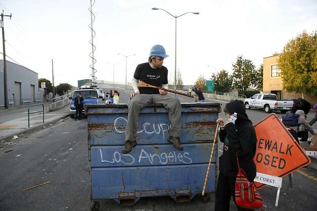 Aaron Thomas, of Oakland, sits on top of a dumpster at the barricade at 3rd Street and Adeline early Thursday, November 3, 2011 in Oakland, Calif. Photo: Beck Diefenbach, Special To The Chronicle