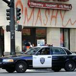 A police cruiser turns onto Broadway from 14th Street in front of the RiteAid drug store, which suffered major damage, in Oakland, Calif. on Thursday, Nov. 3, 2011. A general strike called by Occupy Oakland organizers turned ugly after midnight resulting in widespread damage throughout the downtown area.
