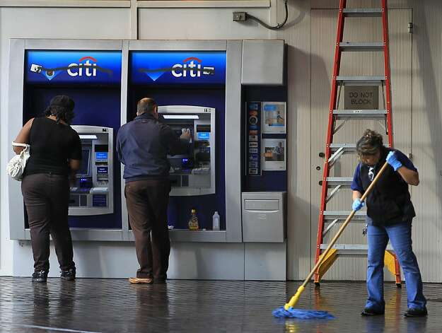 A woman uses an ATM (left) while workers clean up at the Citibank branch at 14th and Broadway streets in Oakland, Calif. on Thursday, Nov. 3, 2011. A general strike called by Occupy Oakland organizers turned ugly after midnight resulting in widespread damage throughout the downtown area. Photo: Paul Chinn, The Chronicle