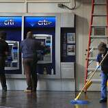 A woman uses an ATM (left) while workers clean up at the Citibank branch at 14th and Broadway streets in Oakland, Calif. on Thursday, Nov. 3, 2011. A general strike called by Occupy Oakland organizers turned ugly after midnight resulting in widespread damage throughout the downtown area.