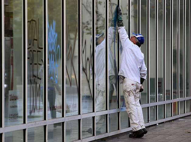 A city employee removes graffiti from the walgreens store at 14th and Broadway in Oakland, Calif. on Thursday, Nov. 3, 2011. A general strike called by Occupy Oakland organizers turned ugly after midnight resulting in widespread damage throughout the downtown area. Photo: Paul Chinn, The Chronicle