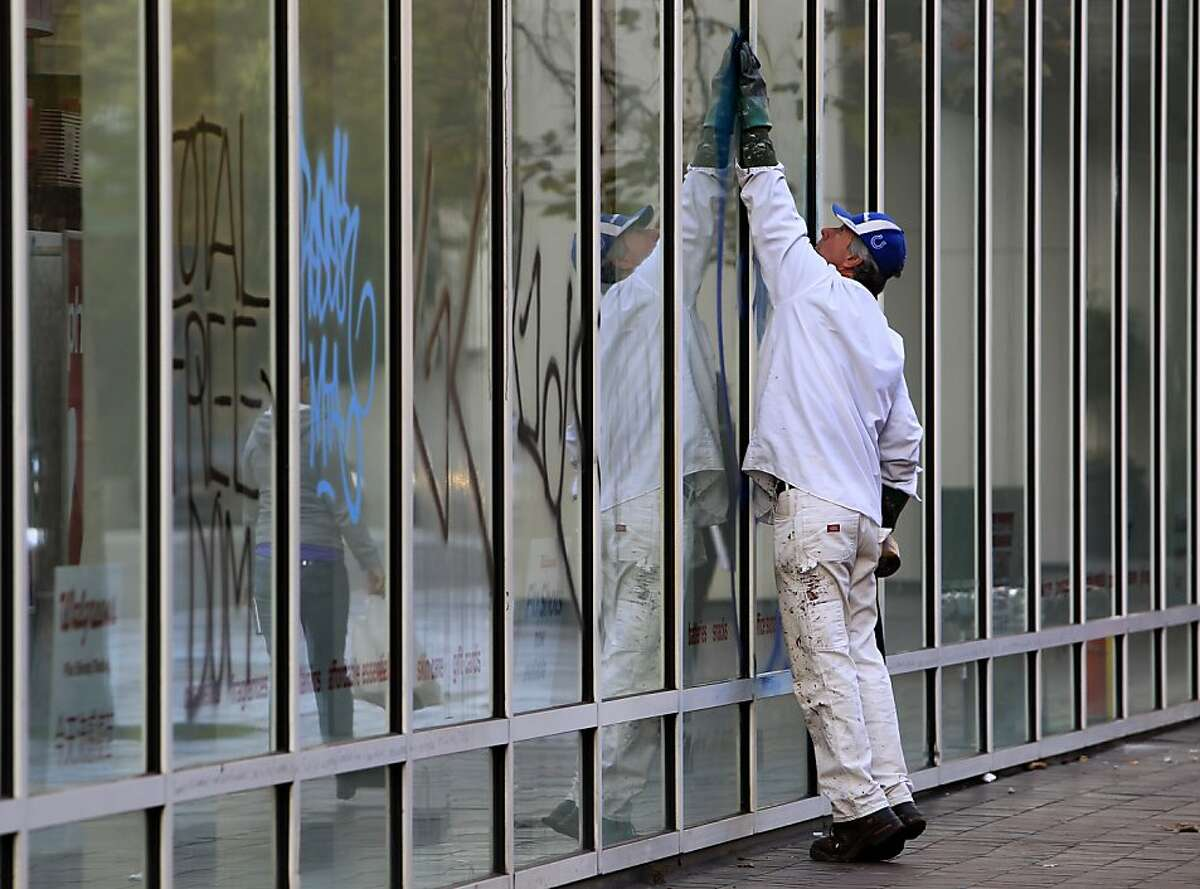 A city employee removes graffiti from the walgreens store at 14th and Broadway in Oakland, Calif. on Thursday, Nov. 3, 2011. A general strike called by Occupy Oakland organizers turned ugly after midnight resulting in widespread damage throughout the downtown area.