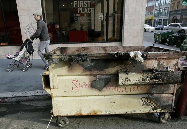 A man walks a baby stoller past a burned dumpster on 16th Street in Oakland, Calif. on Thursday, Nov. 3, 2011. A general strike called by Occupy Oakland organizers turned ugly after midnight resulting in widespread damage throughout the downtown area. Photo: Paul Chinn, The Chronicle
