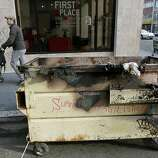 A man walks a baby stoller past a burned dumpster on 16th Street in Oakland, Calif. on Thursday, Nov. 3, 2011. A general strike called by Occupy Oakland organizers turned ugly after midnight resulting in widespread damage throughout the downtown area.