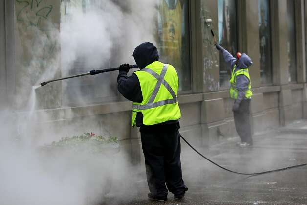 A crew working for the Community Business District removes graffiti from a building at 14th and Broadway streets after overnight violence by Occupy Oakland protesters in Oakland, Calif. on Thursday, Nov. 3, 2011. Photo: Paul Chinn, The Chronicle