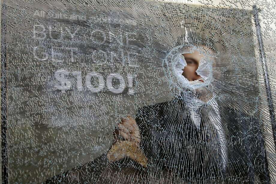 Broken glass is shown at a Men's Warehouse building in downtown Oakland, Calif., Thursday, Nov. 3, 2011 after a Occupy Wall Street protest earlier.  Cleanup work is under way at Oakland's city hall plaza the morning after a massive anti-Wall Street protest turned violent and chaotic.  Graffiti is covering a number of businesses in the immediate area around Frank Ogawa Plaza, where thousands had gathered for a mostly peaceful protest Wednesday. Some windows also are broken, and debris is littering the street. (AP Photo/Paul Sakuma) Photo: Paul Sakuma, AP