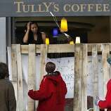 Volunteer clean up crews (below) speak an individual inside of the Tully's Coffee shop which was vandalized the night prior on Thursday, November 3, 2011 in Oakland, Calif.