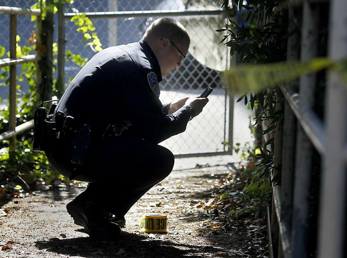 FILE - San Francisco police officer Joshua Enea investigates a crime scene in 2011. On Wednesday, July 26, 2017, Enea, 37, of Antioch, was charged with one count of possessing child or youth pornography, according to the Contra Costa County District Attorney's office.