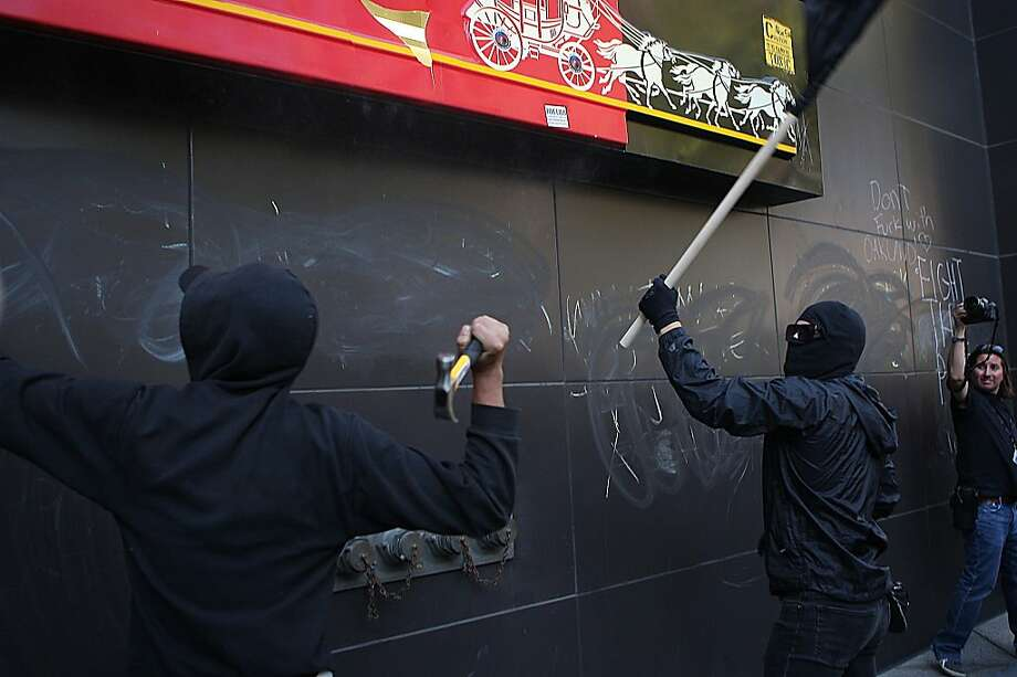 Protesters hit the walls of Wells Fargo Bank on Broadway during the General Assembly of Occupy Oakland in Oakland, Calif., on Wednesday, November 2, 2011. Photo: Liz Hafalia, The Chronicle