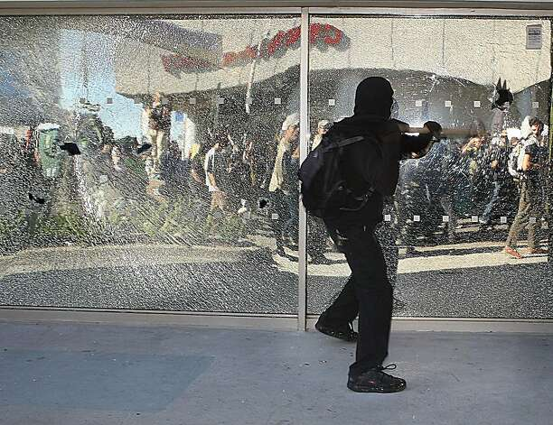 A protester breaks the windows of Citibank during the afternoon anti capitlism march while heading down Webster St. during the General Assembly of Occupy Oakland in Oakland, Calif., on Wednesday, November 2, 2011. Photo: Liz Hafalia, The Chronicle