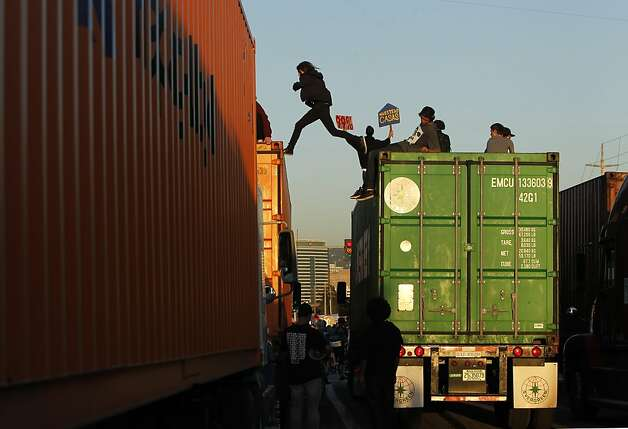 A protester jumps between stopped big rigs at the Port of Oakland. Occupy Oakland protesters numbering in the thousands shut down the Port of Oakland on Wednesday, November 2, 2011, during the General Strike. Photo: Lacy Atkins, The Chronicle