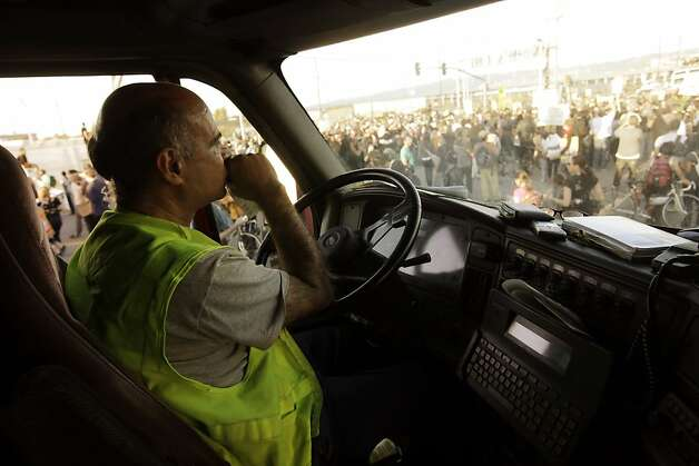 "Moe Nejad, a driver for Kamal Trucking, watches as protesters block the entrance to the Port of Oakland. He says, ""I'm with them, everybody's hurting."" Occupy Oakland protesters numbering in the thousands shut down the Port of Oakland on Wednesday, November 2, 2011, during the General Strike. Photo: Lacy Atkins, The Chronicle"