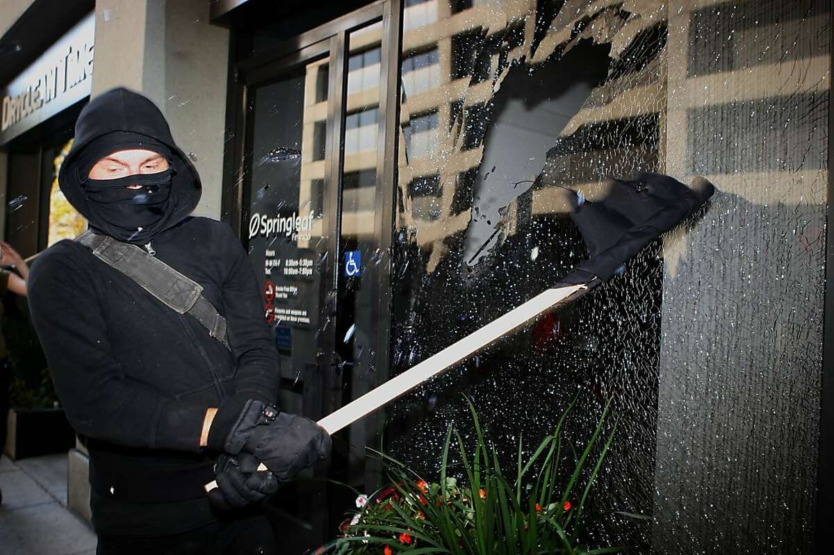 A protester breaks the windows of Springleaf financial bank on Webster St. during the afternoon march of the General Assembly of Occupy Oakland in Oakland, Calif., on Wednesday, November 2, 2011.
