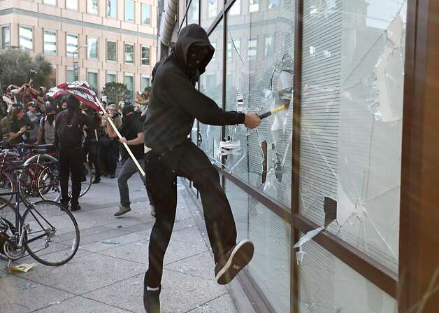 A masked Occupy Oakland protester smashes a window at a Wells Fargo Bank in Oakland during a citywide general strike on November 2, 2011 in California. AFP Photo / Kimihiro Hoshino (Photo credit should read KIMIHIRO HOSHINO/AFP/Getty Images) Photo: Kimihiro Hoshino, AFP/Getty Images