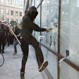 A masked Occupy Oakland protester smashes a window at a Wells Fargo Bank in Oakland during a citywide general strike on November 2, 2011 in California. AFP Photo / Kimihiro Hoshino (Photo credit should read KIMIHIRO HOSHINO/AFP/Getty Images)