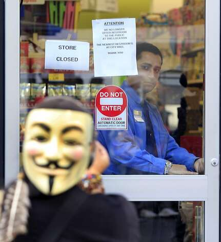 A Walgreens employee locked the doors to the drug store during a general strike by Occupy Oakland protesters in Oakland, Calif. on Wednesday, Nov. 3, 2011. Photo: Paul Chinn, The Chronicle