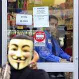 A Walgreens employee locked the doors to the drug store during a general strike by Occupy Oakland protesters in Oakland, Calif. on Wednesday, Nov. 3, 2011.