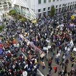 Thousands of Occupy Oakland protesters march past the Elihu Harris State Building on Clay Street during the movement's general strike in Oakland, Calif. on Wednesday, Nov. 3, 2011.