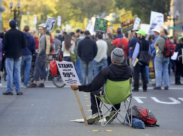 Dominic Santiago sets up his chair in the middle of Broadway Street while Occupy Oakland hold a general strike in Oakland, Calif. on Wednesday, Nov. 3, 2011. Photo: Paul Chinn, The Chronicle
