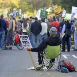 Dominic Santiago sets up his chair in the middle of Broadway Street while Occupy Oakland hold a general strike in Oakland, Calif. on Wednesday, Nov. 3, 2011.