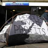 Occupy Oakland protesters pitch a tent in front of a Citibank branch at 12th and Broadway streets during a general strike in Oakland, Calif. on Wednesday, Nov. 3, 2011.