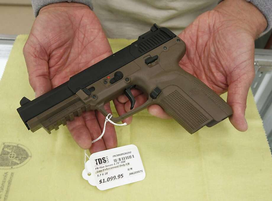 A Belgian-made FN semi-automatic pistol, that can only be purchased in California by law enforcement officers, is displayed for a photo at TDS Guns in Rocklin, Calif., on Tuesday, Nov. 8, 2011. A federal investigation into weapons-dealing in three Sacramento-area law enforcement agencies has opened a window on exemptions in California law that let peace officers buy guns, high-capacity magazines, short-barreled shotguns and even assault weapons that are illegal for average citizens. Peace officers are also allowed to purchase handguns, like the one displayed, that aren't among the 1,319 models certified by the state Department of Justice as having met firing, safety and drop tests. (AP Photo/Rich Pedroncelli)  Ran on: 11-09-2011 This Belgian semiautomatic pistol is legal for purchase only by law officers. Photo: Rich Pedroncelli, AP