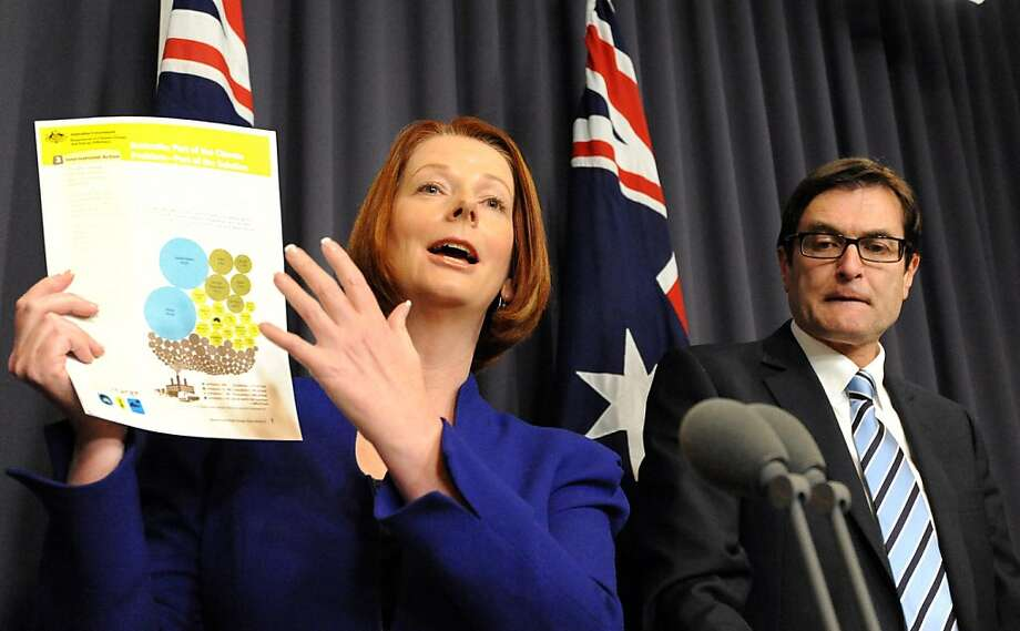 (FILES) Australia Prime Minister Julia Gillard (L) presents the government's carbon emissions fact sheets next to Minister for Climate Change Greg Combet (R) at Parliament House in Canberra on June 14, 2011.  Australia's parliament approved a controversial pollution tax on November 8, 2011, after years of bitter debate over the reform which is aimed at lowering carbon emissions blamed for climate change.          AFP PHOTO / Torsten BLACKWOOD (Photo credit should read TORSTEN BLACKWOOD/AFP/Getty Images) Photo: Torsten Blackwood, AFP/Getty Images