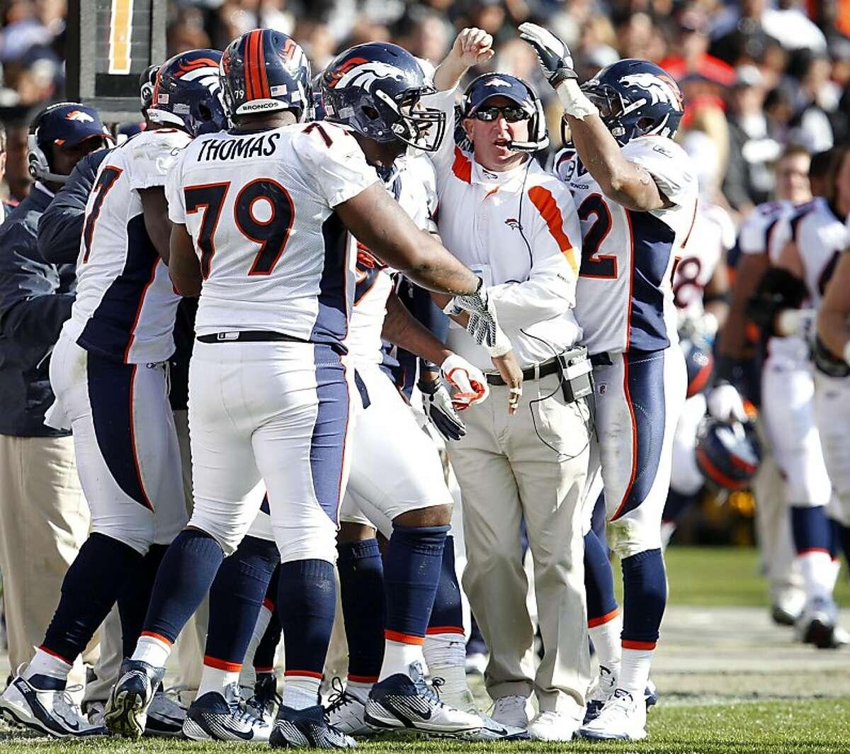 The Denver Broncos team and heach coach John Fox, center cheer as they defeat the Oakland Raiders, Sunday November 6, 2011, at O.co Coliseum in Oakland, Calif. The Broncos defeated the Raiders 38 to 24.