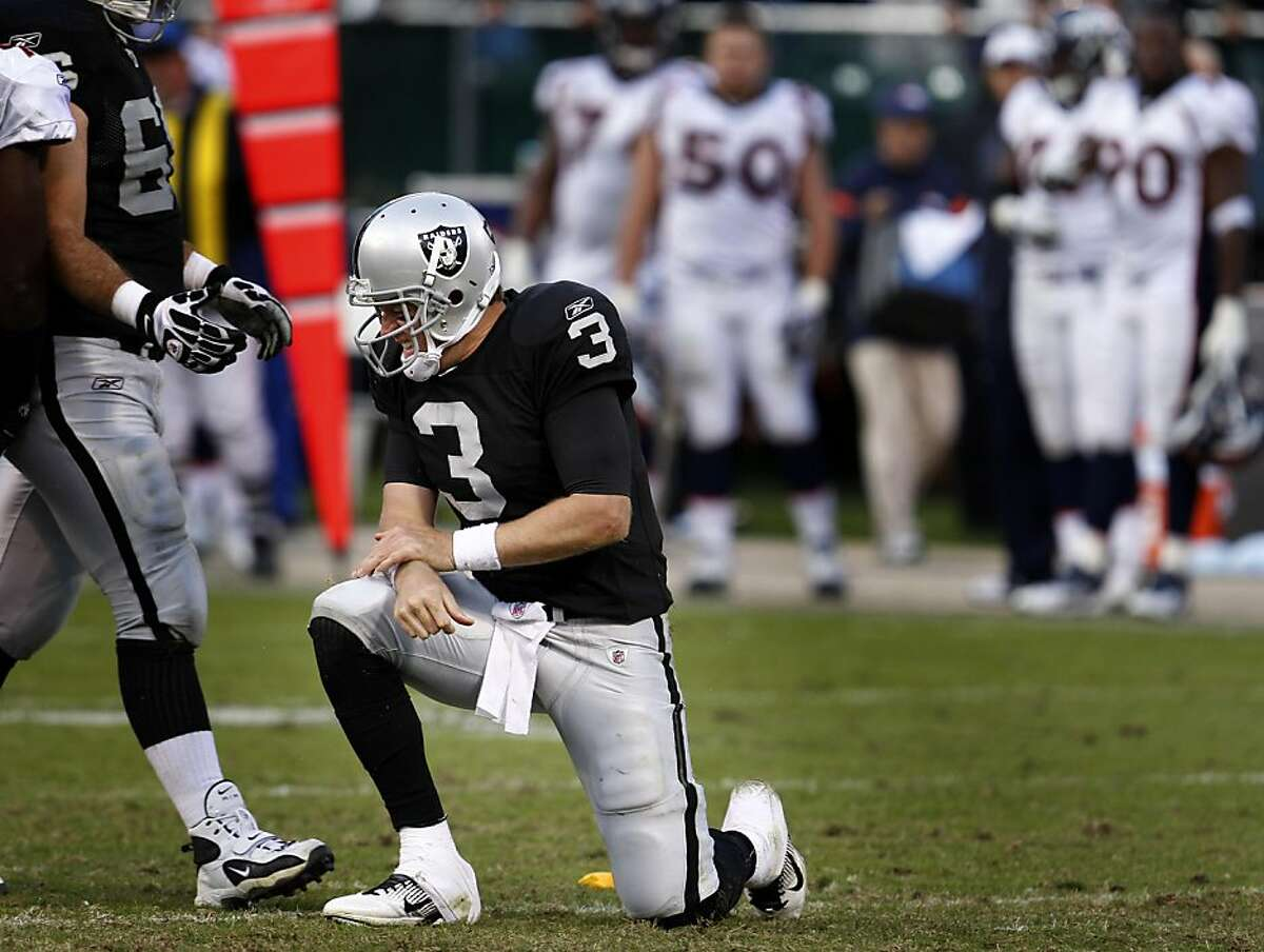 Oakland Raiders quarterback Carson Palmer gets knocked to the ground in the second half against the Denver Broncos, Sunday November 6, 2011, at O.co Coliseum in Oakland, Calif. After being ahead at the half the Raiders lost to the Broncos 38 to 24.