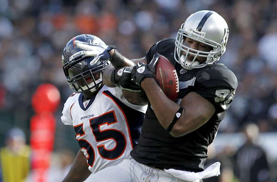 Oakland Raiders Marcel Reece catches a 40 yard pass for a touchdown as he in guarded by Denver Broncos D.J. Williams  in the second quarter, Sunday November 6, 2011, at O.co Coliseum in Oakland, Calif. Photo: Lacy Atkins, The Chronicle