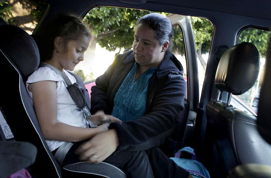 Fairmont Elementary School Secretary Yuri Sanchez buckles her  daughter Michelle, 6- years-old, into the car after school, Monday November 7, 2011, in San Francisco, Calif.  On Monday the Census Bureau announced a new supplemental poverty measure that takes into account real-life factors that affect people's income such as costs of living, healthcare expenses and government benefits. This provides a more accurate picture of poverty in the U.S. . Sanchez, who works full time and whose husband is a construction worker and often doesn't have work falls into this category. Photo: Lacy Atkins, The Chronicle