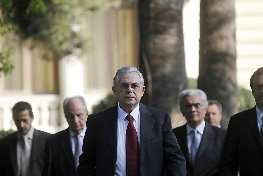 Lucas Papademos, the former vice president of the European Central Bank (ECB), center, leaves the Greek presidential palace after meeting with other party leaders in Athens, Greece, on Thursday, Nov. 10, 2011. Papademos was chosen to lead a new Greek unity government, paving the way for a coalition charged with securing additional financing to avert the country's economic collapse. Photographer: Kostas Tsironis/Bloomberg *** Local Caption *** Lucas Papademos Photo: Kostas Tsironis, Bloomberg