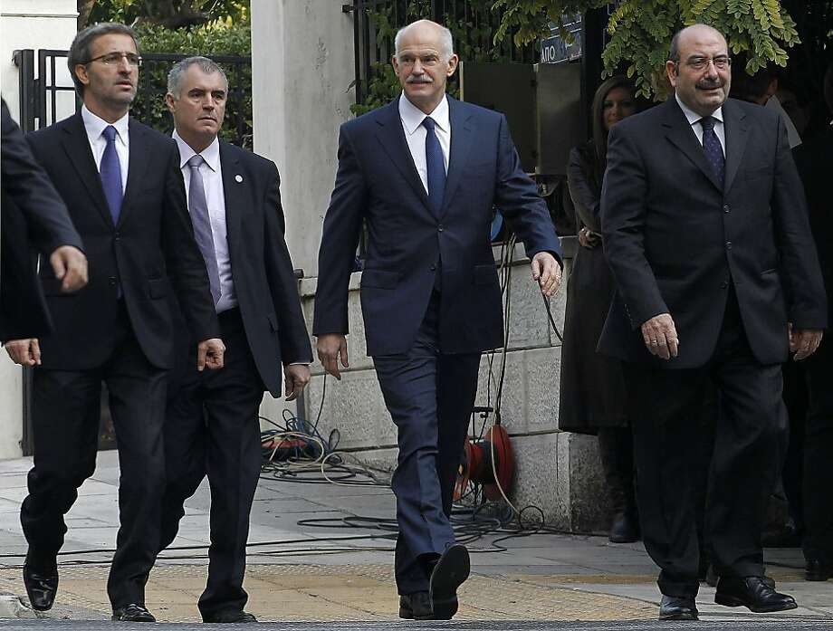 Outgoing Greek Prime Minister George Papandreou, center, is accompanied by his advisors and security detail as he arrives at the presidential palace for a meeting between political parties led by Greek President Karolos Papoulias in Athens, Thursday, Nov. 10, 2011. The hope is that the fourth day of talks will finally yield a new prime minister to head an interim government that will secure the country's continued bailout funding. (AP Photo/Petros Giannakouris) Photo: Petros Giannakouris, AP