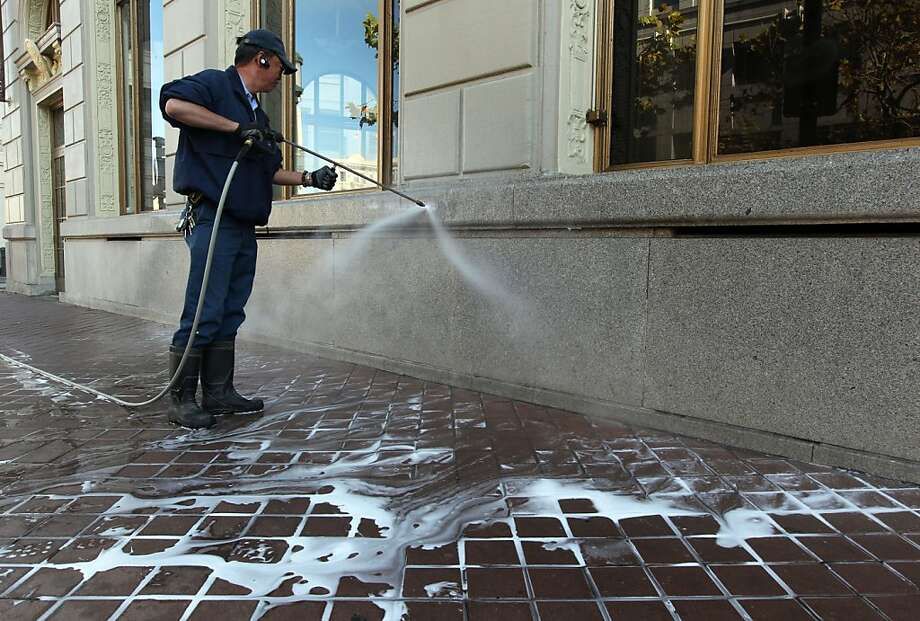 Gary Wong cleans off graffiti from the Westlake Building next to Frank Ogawa Plaza in Oakland Friday, November 4, 2011. The damage was part o0f the demonstrations earlier in the week. Photo: Lance Iversen, The Chronicle