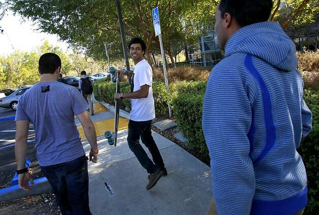 Niket Desai (center) of Punchd walks with his skateboard on the Google campus and looks back at friend Qasar Younis (right) of TalkBin. Google has already acquired 57 companies including Dealmap, TalkBin and Punchd.  Their employees are now working at the huge Mountain View campus and seem to be enjoying the ambience. Photo: Brant Ward, The Chronicle