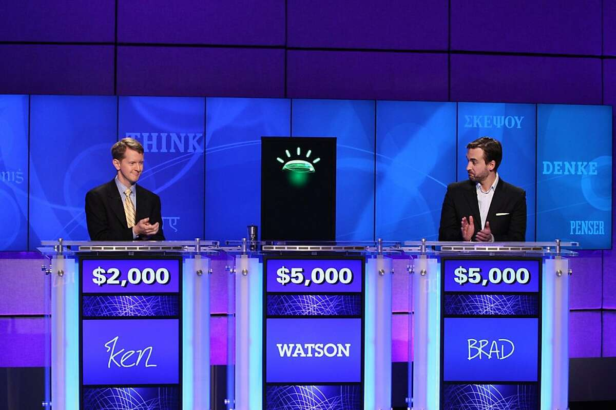 In this undated publicity image released by Jeopardy Productions, Inc., contestants Ken Jennings, left, and Brad Rutter and a computer named Watson compete on the game show