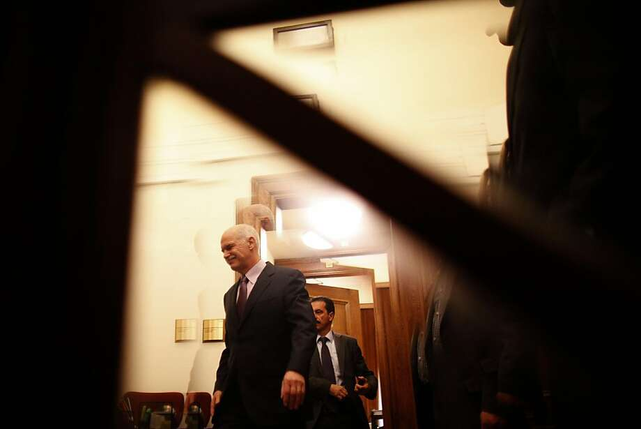 Greece's Prime Minister George Papandreou, left, is seen through a door window as he enters a cabinet meeting at the parliament in Athens on Sunday, Nov. 6, 2011. Greek leaders struggled for a second day to end an ongoing political crisis, under intense pressure to ensure the country doesn't go bankrupt in the next few weeks and that it remains in the eurozone. Papandreou informed cabinet members that he asked Greek President Karolos Papoulias for an urgent meeting with opposition leader Antonis Samaras. (AP Photo/Kostas Tsironis) Photo: Kostas Tsironis, AP