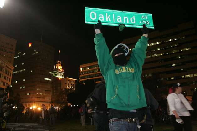 An Occupy Oakland protester holds an Oakland street sign at Frank Ogawa Plaza on Wednesday, Oct. 26, 2011, in Oakland, Calif. Photo: Mathew Sumner, Special To The Chronicle