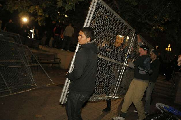 Occupy Oakland protestors carry a fence that circled Frank Ogawa Plaza in front of City Hall in Oakland, Calif., on Wednesday, Oct. 27, 2011.  After hours of discussion, some protestors took it upon themselves to tear the fence down. Photo: Dylan Entelis, The Chronicle