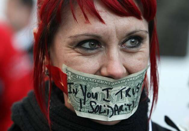 An Occupy Oakland protester wears a dollar bill with a message on it on her mouth in Frank Ogawa Plaza on Wednesday, Oct. 26, 2011, in Oakland, Calif. Photo: Mathew Sumner, Special To The Chronicle