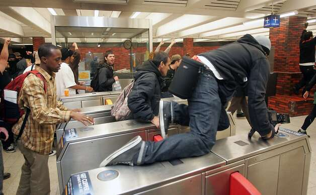 Occupy Oakland protesters jump the gates at a BART station in an attempt to ride free to San Franicsco on Wednesday, Oct. 26, 2011, in Oakland, Calif. Photo: Mathew Sumner, Special To The Chronicle