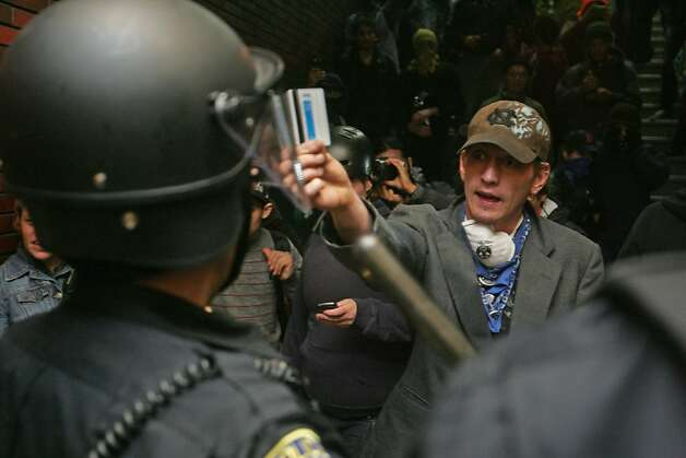 An Occupy Oakland protester shows his ticket to a BART Police Officer after officials closed the station to prevent the rush of protesters from getting on the system on Wednesday, Oct. 26, 2011, in Oakland, Calif. Photo: Mathew Sumner, Special To The Chronicle