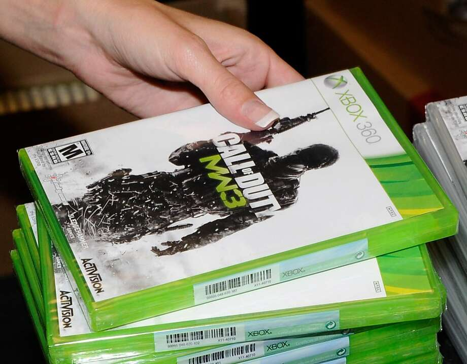 """NORTH LAS VEGAS, NV - NOVEMBER 08:  GameStop employee Randi Taber rings up copies of """"Call of Duty: Modern Warfare 3"""" for the Xbox 360 during a launch event for the highly anticipated video game at a GameStop Corp. store November 8, 2011 in North Las Vegas, Nevada. Video game publisher Activision released the eighth installment in the '""""Call of Duty"""" franchise at midnight.  (Photo by Ethan Miller/Getty Images) Photo: Ethan Miller, Getty Images"""