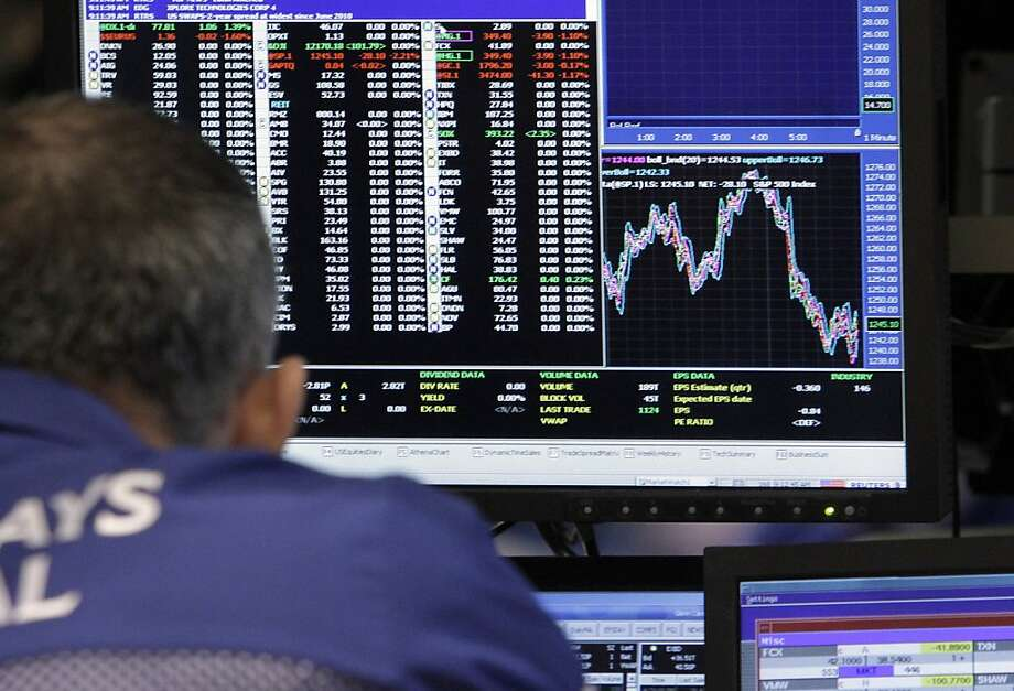 A specialisgt works at his post on the floor of the New York Stock Exchange Wednesday, Nov. 9, 2011. The Dow Jones industrial average lost more than 240 points in early trading after Italy's borrowing costs soared.(AP Photo/Richard Drew) Photo: Richard Drew, AP