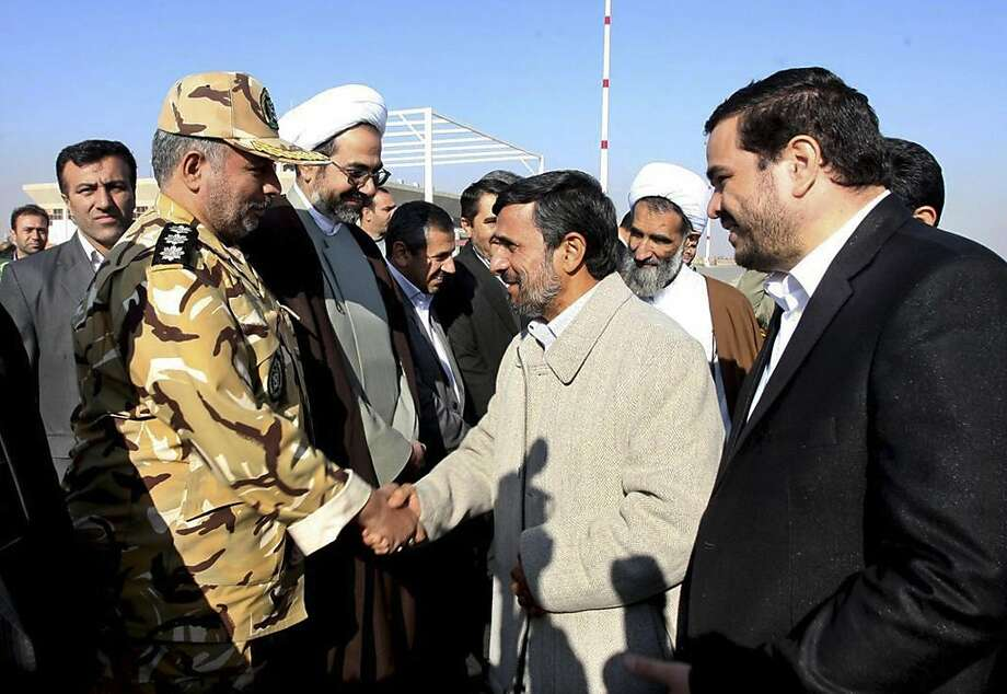 "In this image provided by the Presidency Office, Iranian President Mahmoud Ahmadinejad, second right, shakes hands with an unidentified army colonel as he arrives at the Shahr-e-Kord, during his provincial tour, in central Iran, Wednesday, Nov. 9, 2011. Iran won't retreat ""one iota"" from its nuclear program but the world is being misled by claims that it seeks atomic weapons, President Mahmoud Ahmadinejad said Wednesday in his first reaction since a U.N. watchdog report that Tehran is on the brink of developing a warhead. (AP Photo/Presidency Office, Ebrahim Seyyedi)  EDITORIAL USE ONLY, NO SALES Photo: Ebrahim Seyyedi, AP"