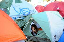 Occupy Oakland camper Lucas Enos smokes a cigarette in his tent on Monday, Nov. 7, 2011, in Oakland, Calif.