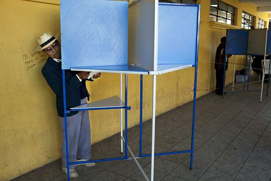 A man peers from a voting booth before casting his vote during Guatemala's presidential runoff election, in San Juan Comalapa, Guatemala, Sunday Nov. 6, 2011. Polls showed Otto Perez Molina, 61, a retired general and former military intelligence director at least 10 points ahead of Manuel Baldizon, a 41-year-old tycoon turned political populist. (AP Photo/Rodrigo Abd) Photo: Rodrigo Abd, AP